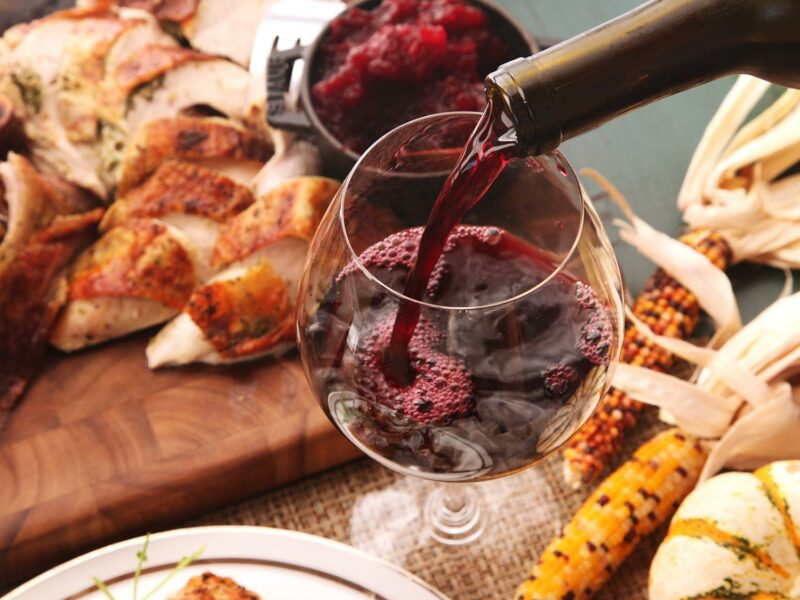 Thanksgiving spread while pouring red wine in a glass