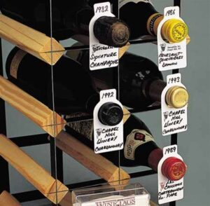 Five wine bottles on a wine rack with eight shelves for wine, five of the bottles have wine tags on the neck of the bottle.