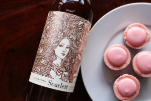 Close up of Rosé bottle and plate of four strawberry cheesecake bites