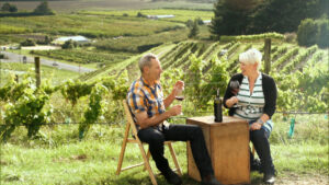 A man and woman sitting at a small wood table in wood chairs with a vineyard in the background