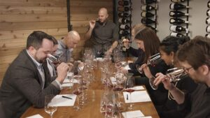 A group of eight people around a table smelling and tasting wine