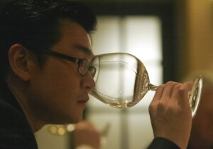 A side profile of Rudy Kurniawan smelling a glass of white wine