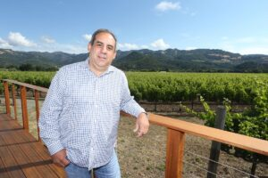 Chris Madrigal from Madrigal Wines posing on a deck with vineyards and a mountain in the background