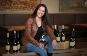 Theresa Heredia Winemaker from Gary Farrell Winery sitting on a table with six bottles of wine around her as she holds a glass