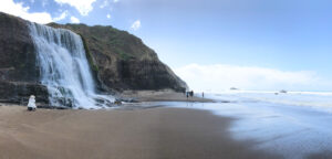 Scene of Alamere Falls in California, a beach with a waterfall and ocean in the distance